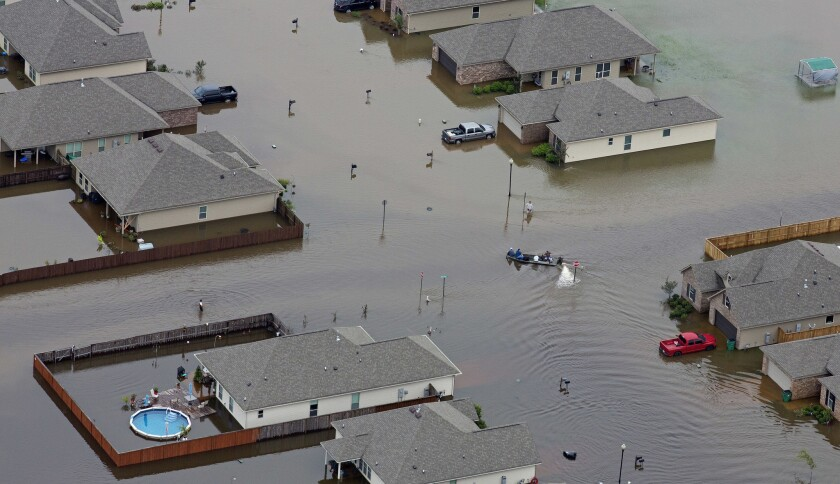 A boat motors between flooded homes after heavy rains inundate the region in Hammond, La.