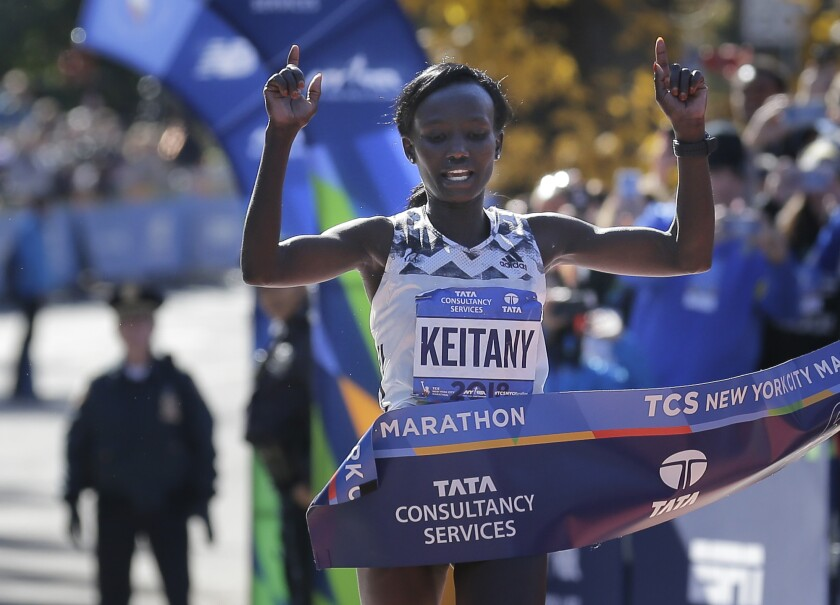 FILE - Mary Keitany of Kenya crosses the finish line first in the women's division of the New York City Marathon in New York, in this Sunday, Nov. 4, 2018, file photo. Marathon runner Mary Keitany retired from the sport on Wednesday, Sept. 22, 2021, because of a back injury, ending a career in which she won multiple races in London and New York and set the world record for a women-only race. (AP Photo/Seth Wenig, File)