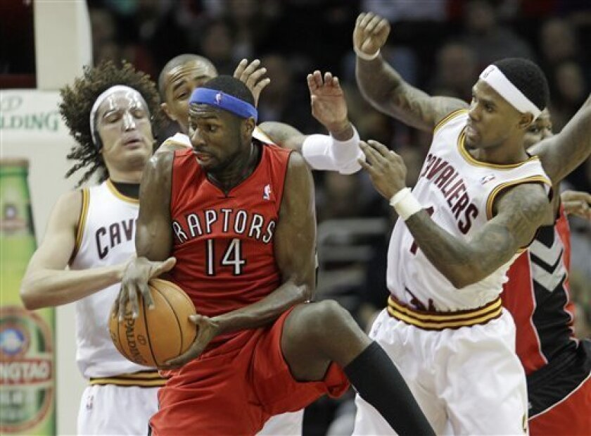 Toronto Raptors' Julian Wright grabs a rebound ahead of Cleveland Cavaliers' Anderson Varejao, left, from Brazil, abd Daniel Gibson, right, in the second quarter in an NBA basketball game Wednesday, Jan. 5, 2011, in Cleveland. (AP Photo/Tony Dejak)