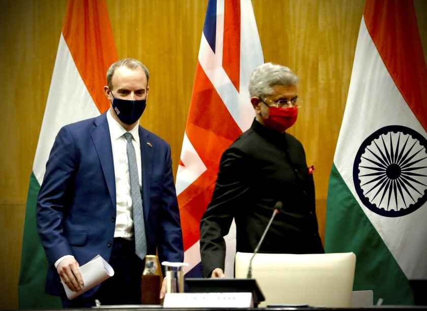 British Foreign Secretary Dominic Raab, left and Indian Minister of External Affairs Subrahmanyam Jaishankar arrive to make joint press statements after their meeting in New Delhi, India, Tuesday, Dec.15, 2020. (AP Photo/Manish Swarup)