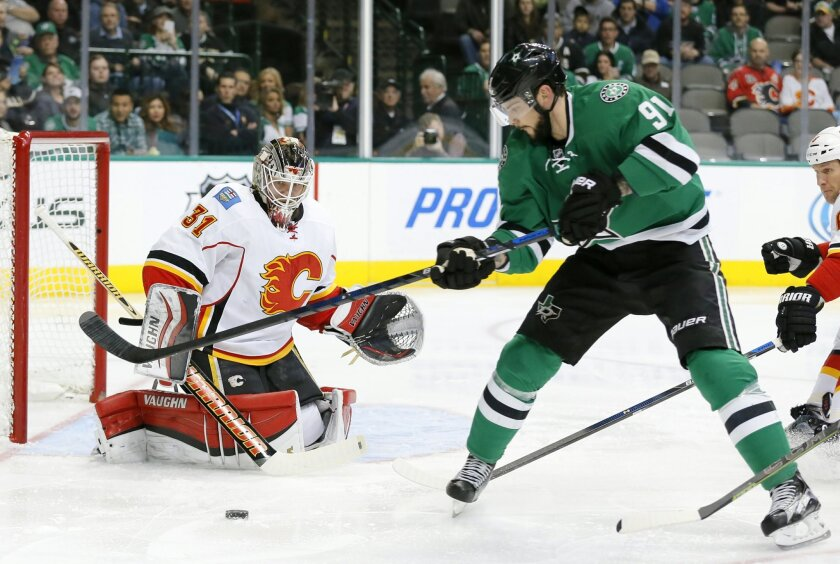 Calgary Flames goalie Karri Ramo (31) of Finland keeps track of the puck as Dallas Stars center Tyler Seguin (91) pressures the net in the first period of an NHL hockey game, Monday, Jan. 25, 2016, in Dallas. (AP Photo/Tony Gutierrez)
