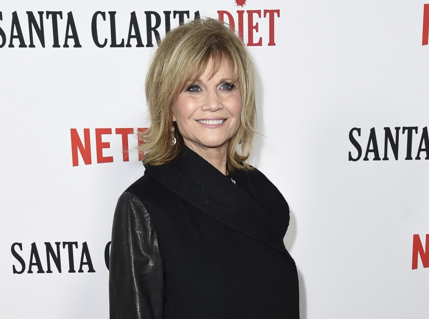Markie Post in a dress covered by a long jacket