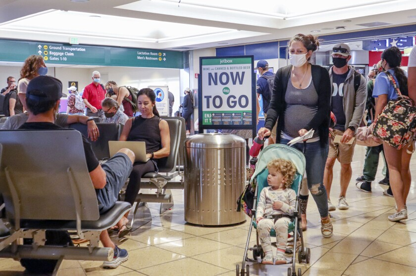 Passengers, some with and without masks, walk through the termial area at San Diego International Airport.
