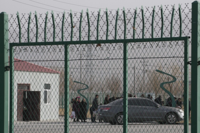 FILE - In this Monday, Dec. 3, 2018, file photo, people line up at the Artux City Vocational Skills Education Training Service Center at the Kunshan Industrial Park in Artux in western China's Xinjiang region. A small core of international lawyers and activists are prodding leading Olympic sponsors to acknowledge China's widely reported human-rights abuses against Muslim Uyghurs, Tibetans and other minorities.(AP Photo/Ng Han Guan, File)