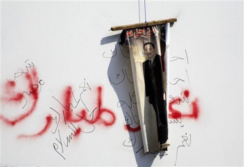 A poster showing President Hosni Mubarak, is hung by anti-government protesters over Arabic slogans supporting Mubarak set by his supporters a week ago in Cairo street, Egypt, Friday, Feb. 11, 2011. Egypt's military threw its weight Friday behind President Hosni Mubarak's plan to stay in office thr