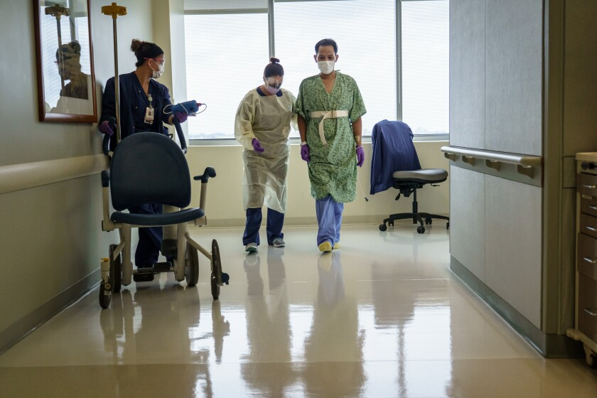In this photo from April, Don Udan walks with assistance from a physical therapist.