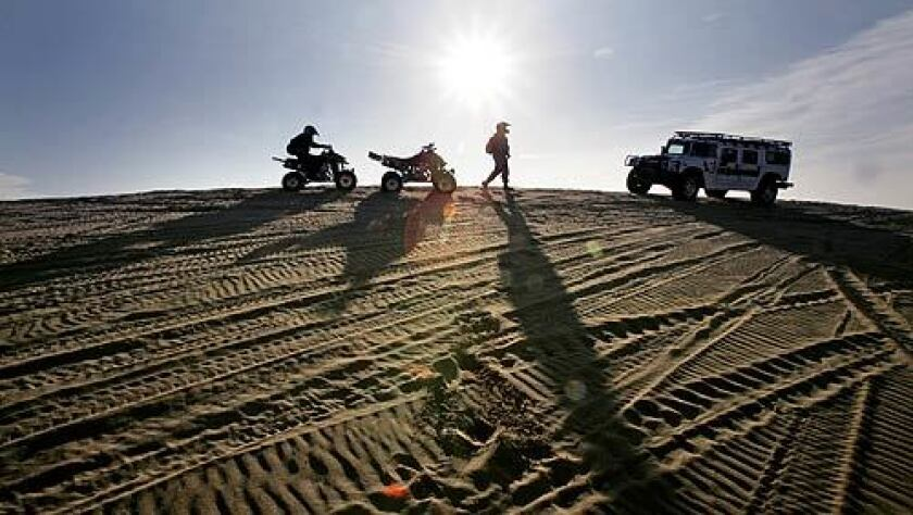 U.S. Border Patrol agents on small ATVs stop to talk with another agent in a Hummer in the Imperial Sand Dunes Recreation Area. It's a 24-hour-a-day enforcement effort to keep smugglers from crossing the unfenced desert borderline.
