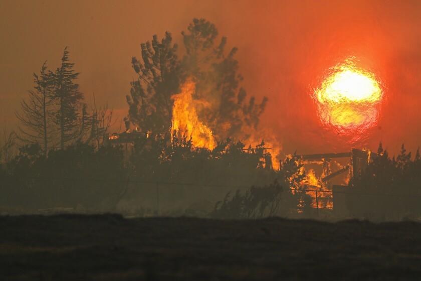 A house on Cima Mesa Road in Juniper Hills burns in the Bobcat fire.