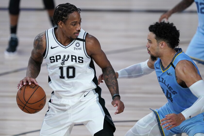 San Antonio Spurs small guard DeMar DeRozan dribbles looks to drive against Memphis Grizzlies guard Dillon Brooks.