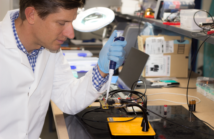 Octavian Florescu, cofounder of In Diagnostics, places a blood sample on the company's prototype diagnostic chip.