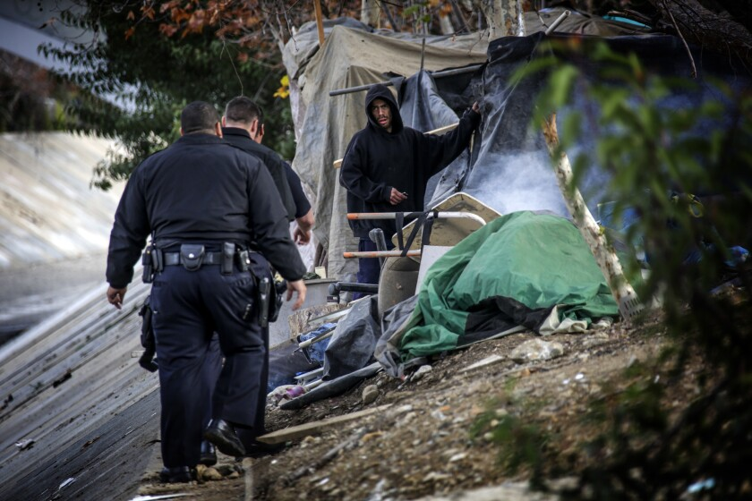 LAPD officers approach a homeless man camped along Arroyo Seco near Avenue 26.