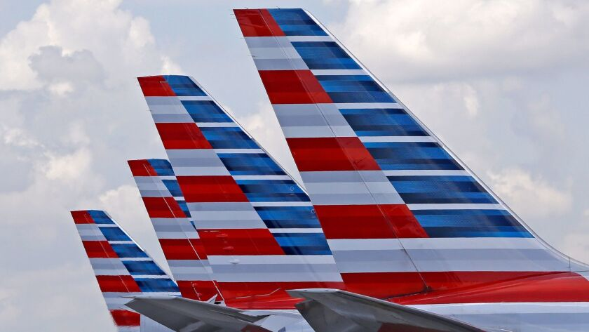 Four American Airlines passenger planes sit parked at Miami International Airport. A computer error has allowed too many pilots at the Fort Worth-based airline to take time off for the Christmas holiday.