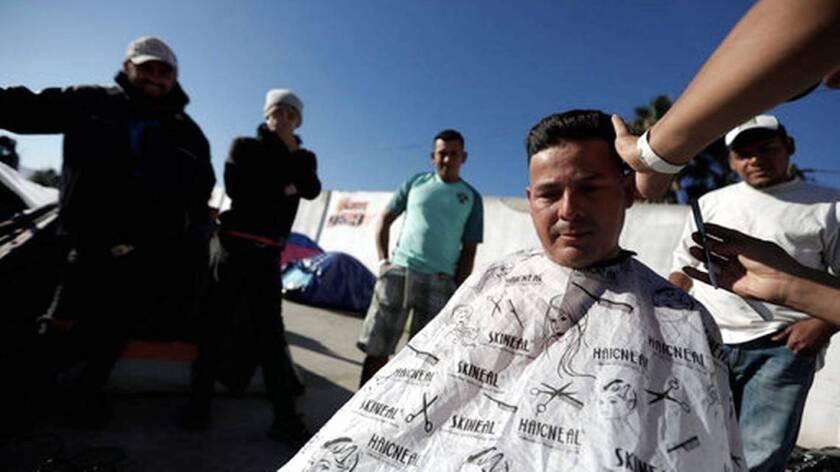 El peluquero hondureño Daniel Villafranca, de 19 años de edad, le corta el cabello a otro inmigrante, Juan Francisco Medrano, mientras otros clientes esperan su turno dentro de la ex sala de conciertos Barretal, que actualmente está habilitada como refugio para más de 2,000 migrantes en Tijuana, México.