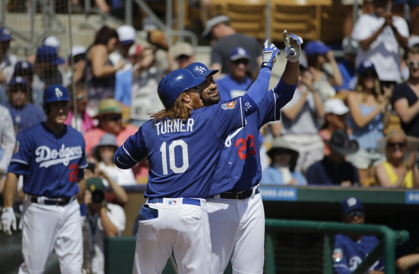 Justin Turner, center, celebrates his home run with Adrian Gonzalez during the first inning of the Dodgers' exhibition game against the Seattle Mariners on Monday.