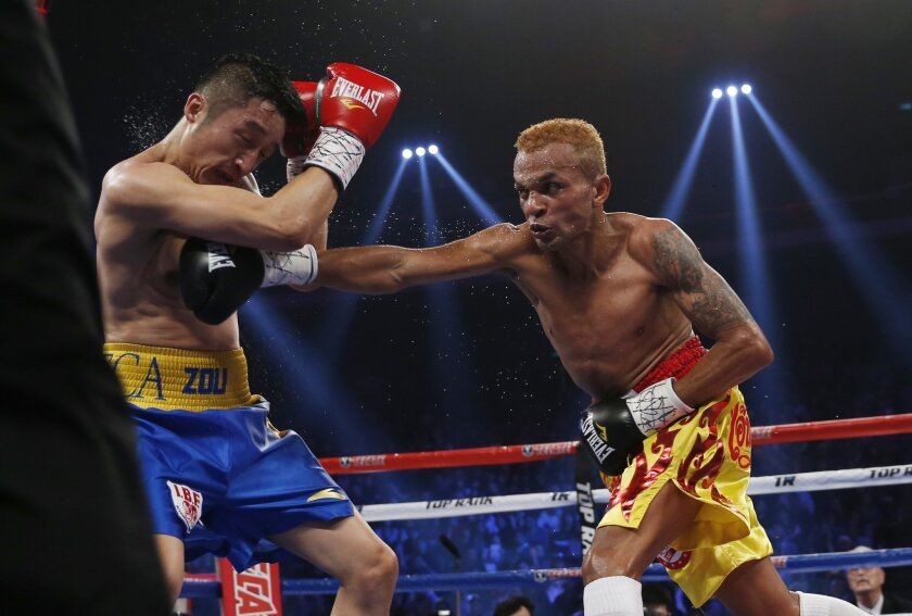 FILE - In this March 7, 2015, file photo, Thailand's Amnat Ruenroeng, right, throws a punch at China's double Olympic gold medalist Zou Shiming during their IBF flyweight title boxing match at the Venetian Macao in Macau. The International Boxing Association's high-profile scheme to entice prominent pros to compete in Rio de Janeiro hasn't worked. Instead of the star-studded tournament many apparently wanted, only a trio of traditional pros accepted the offer to fight for gold medals in Brazil. (AP Photo/Kin Cheung, File)