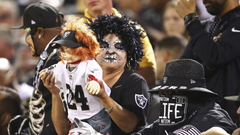 An Oakland Raiders fan holds a Chucky doll during the second half of an NFL football game against th
