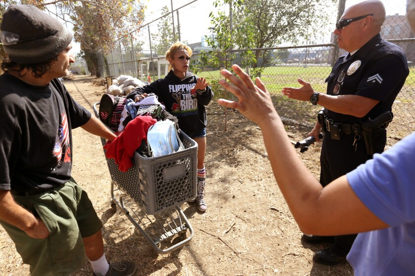 LAPD Officer Austin Fernald talks with Veronica Gonzalez and Miguel Angel Gonzalez along the Arroyo Seco Parkway during a sweep of homeless encampments in June.