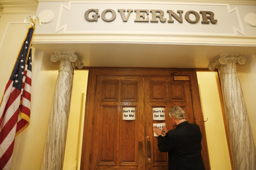 Nathaniel Batchelder of the Oklahoma Coalition Against the Death Penalty places a protest sign outside Gov. Mary Fallin's office at the state Capitol in Oklahoma City.