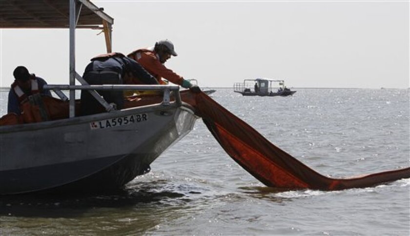 Workers remove containment boom from water contaminated by oil from the Deepwater Horizon spill, Thursday, June 10, 2010, in Bay Barbeau near Chauvin, La. (AP Photo/Eric Gay)