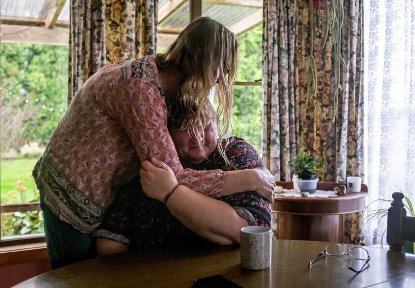 "Carmall Casey, right, is embraced by Maxine Piper, a longtime friend and a source of support through Casey's addiction to opioids and battle with chronic pain, at her home in Black River, Tasmania, Australia, Tuesday, July 23, 2019. Casey doesn't know what she'll do when the pain returns. But she says she will never return to opioids. ""I'm not going back,"" she says and begins to weep. ""I'm not."" (AP Photo/David Goldman)"