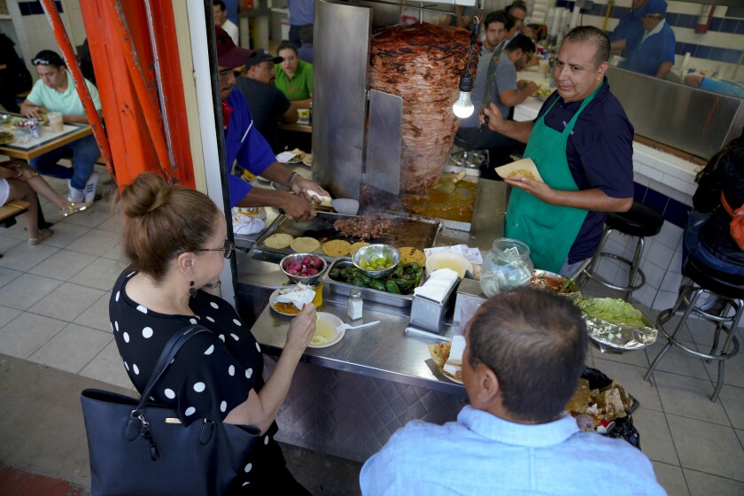 In Tijuana, Mexico, customers are encouraged to sit next to the tacos al pastor grill and order directly from Juan Manuel de Estrada.