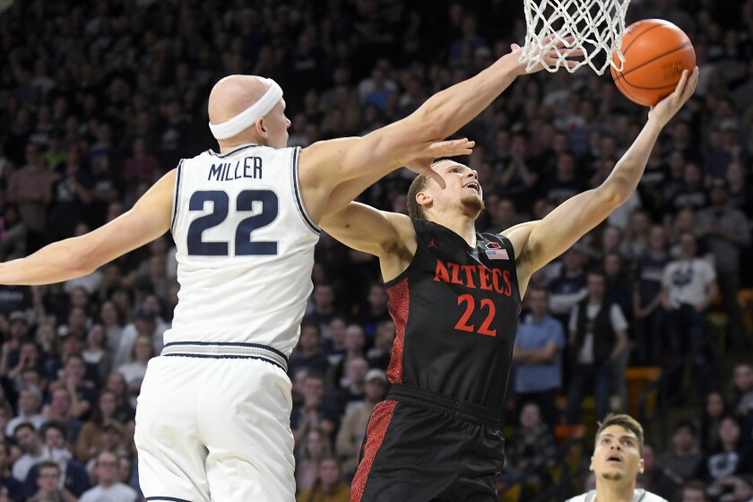 SDSU's Malachi Flynn (right) shoots against Utah State's Brock Miller in the Aztecs' 77-68 win at the Dee Glen Smith Spectrum on Saturday.