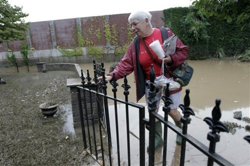 Ellie Martindale, one of the first residents to return, walks in her gate to check on her home after flooding in the Shipoke area caused by the remnants of Tropical Storm Lee Saturday, Sept. 10, 2011 in Harrisburg, Pa. (AP Photo/Alex Brandon)