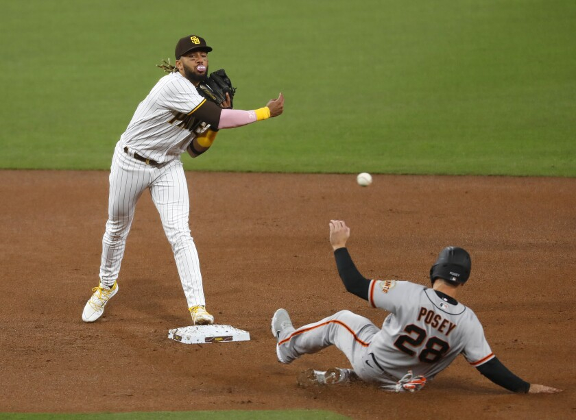 Fernando Tatis Jr. forces Giants' Buster Posey out at second base but is unable to complete double play Monday at Petco Park.