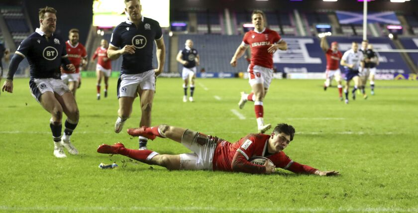 Wales' Louis Rees-Zammit dives in to score his side's fourth try, during the Six Nations rugby union international match between Scotland and Wales, at BT Murrayfield Stadium, in Edinburgh, Scotland, Saturday, Feb. 13, 2021. (Jane Barlow/PA via AP)