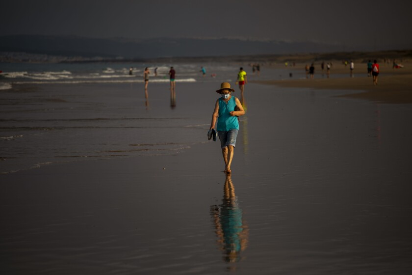 Woman walks on beach in Cadiz province, Spain