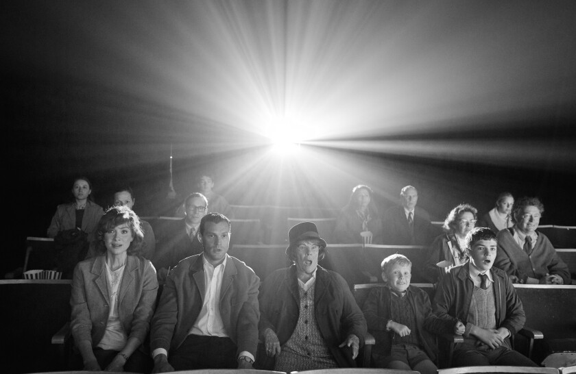 A black-and-white still of people in a movie theater, the projector flashing from behind them.