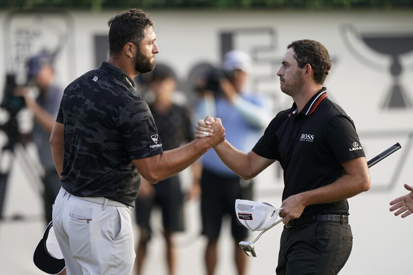 Jon Rahm, left, shakes hands with Patrick Cantlay after the third round of the Tour Championship on Sept. 4, 2021.
