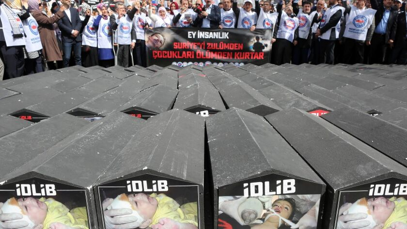 People stand in front of symbolic coffins with pictures of Syrian victims and inscriptions, which tr