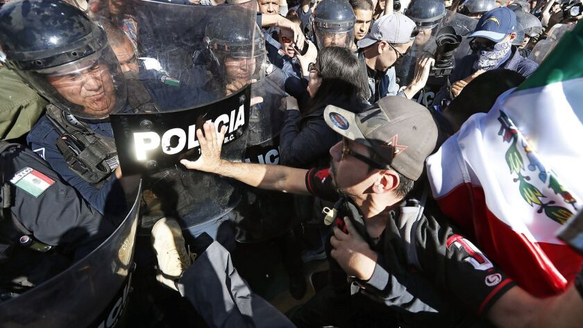 TIJUANA, MEXICO - NOV. 18, 2018. Protesters clash Sunday, Nov. 18, 2018, with police guarding a s