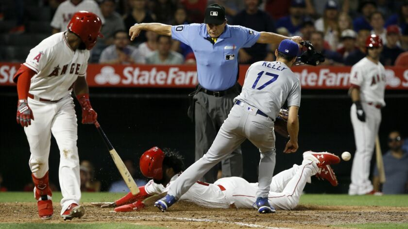 Los Angeles Angels' Brian Goodwin, center, scores on a wild pitch, as the throw back to Los Angeles