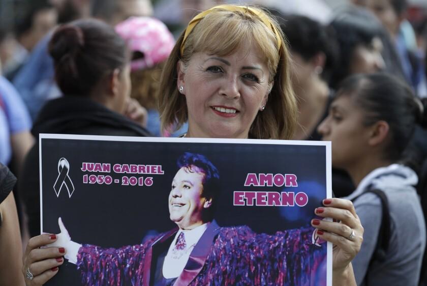 Una mujer sostiene un cartel del compositor y cantante mexicano Juan Gabriel ante el Palacio de Bellas Artes en Ciudad de México, el martes 30 de agosto de 2016. (AP Foto/Eduardo Verdugo)