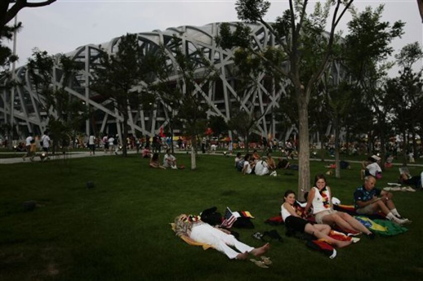 "In this Aug. 20, 2008 file photo, German tourists rest as they wait for an athletic's race to begin, outside the National Stadium, also known as the ""Bird's Nest"" in Beijing, China. The number of travelers to China fell 2 percent last year, government data showed, reflecting the effects of heavy s"