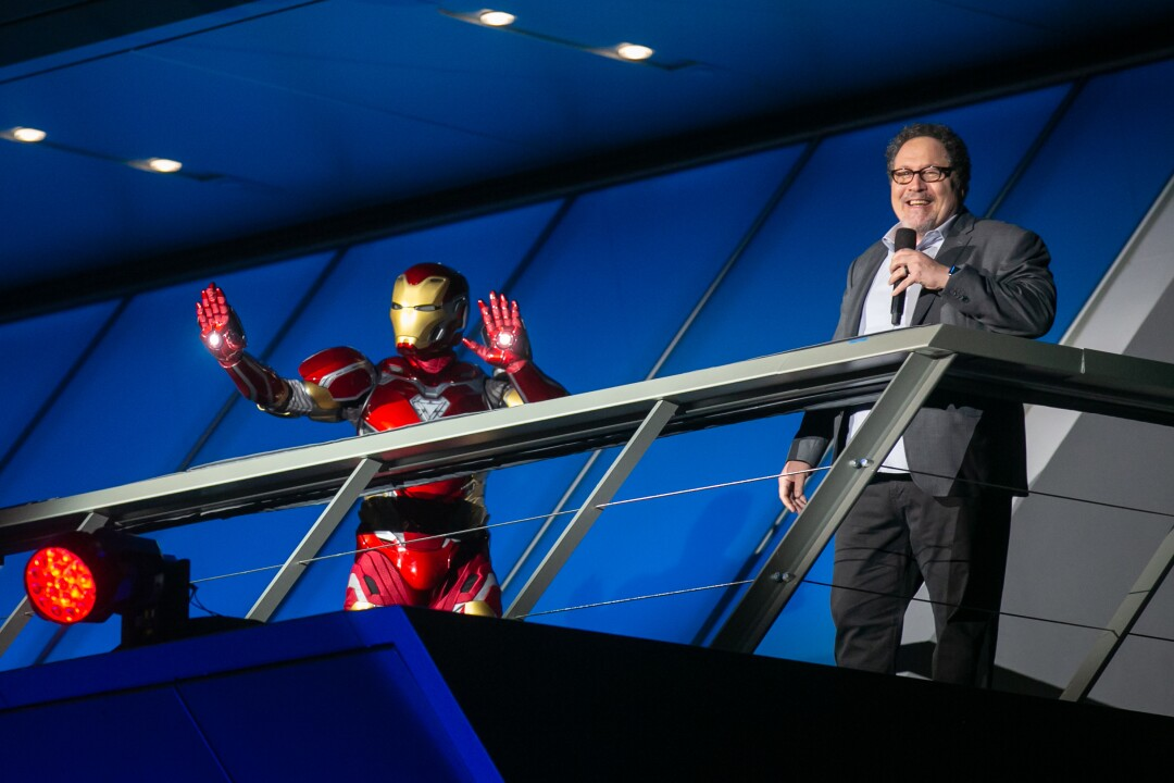 Iron Man holds up his hands onstage as Jon Favreau speaks.
