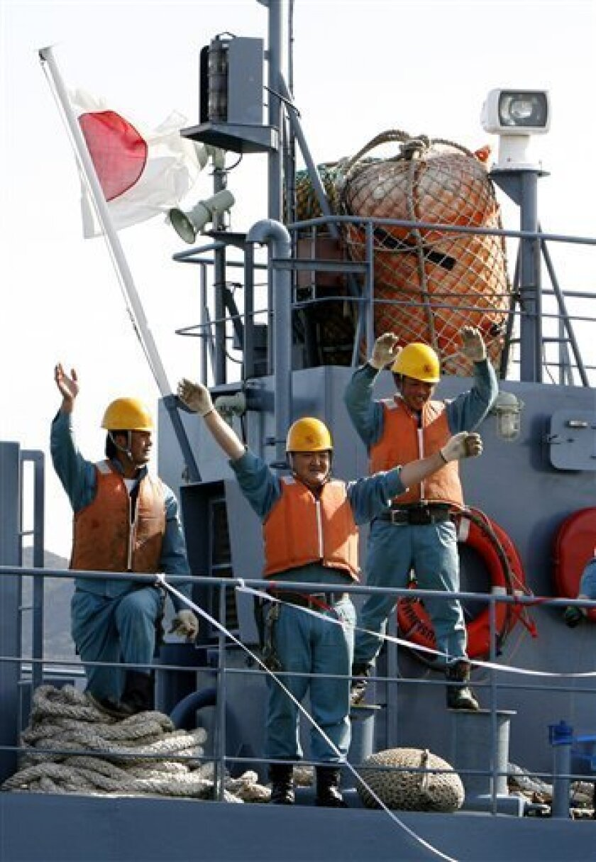In this November 18, 2007, file photo crew members of Japanese whaling vessel Yushin Maru wave as they depart for a hunt at a port of Shimonoseki, southwestern Japan. Japan said Tuesday February 3, 2009, it will reject any proposal by the International Whaling Commission that halts research whaling in the Antarctic, signaling a world body compromise opening limited coastal whaling will not work. (AP Photo/Shizuo Kambayashi, File)