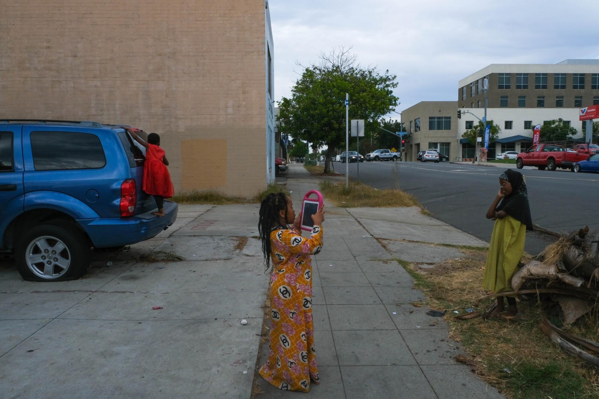 Sadiya, 7, and her cousins Nuriya, 7, and Safiya, 5, take and pose for photographs after class