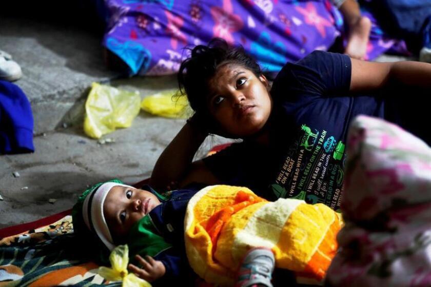 Migrantes hondureños que cruzaron la frontera con Guatemala y se dirigen hacia los Estados Unidos en grupo duermen bajo una carpa en una calle de Esquipulas, Chiquimula afuera de la Casa del Migrante que se encuentra llena. EFE