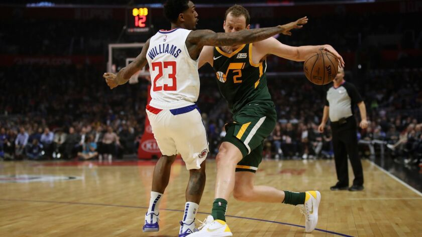 Clippers' Lou Williams (23) defends against the dribble of Utah Jazz's Joe Ingles (2) during the first half at Staples Center on Wednesday.