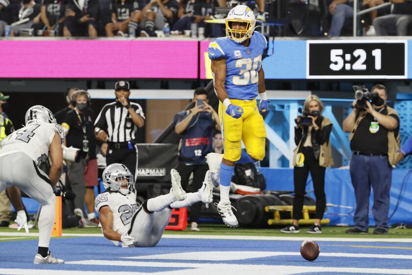 Inglewood CA, Monday, October 4, 2021 - Los Angeles Chargers running back Austin Ekeler (30) scores a touchdown past Las Vegas Raiders safety Trevon Moehrig (25) in the second half at SoFi Stadium. (Robert Gauthier/Los Angeles Times)