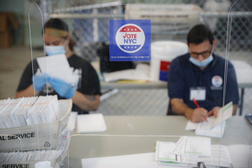 Workers wear personal protective equipment as they check ballots at a Board of Elections facility in New York last week.