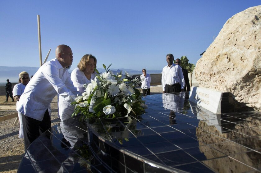 Haiti's President Michel Martelly, left, and first lady Sophia Martelly, center, place a bouquet of flowers at a monument in memory of the victims of the 2010 earthquake, during a memorial service at Titanyen, a mass burial site for earthquake victims, north of Port-au-Prince, Haiti, Sunday, Jan. 12, 2014. Martelly's government issued a decree declaring Jan. 12 a day of remembrance and reflection. The Haitian flag is being flown at half-staff, and clubs are to remain closed. (AP Photo/Jean Marc Herve Abelard)