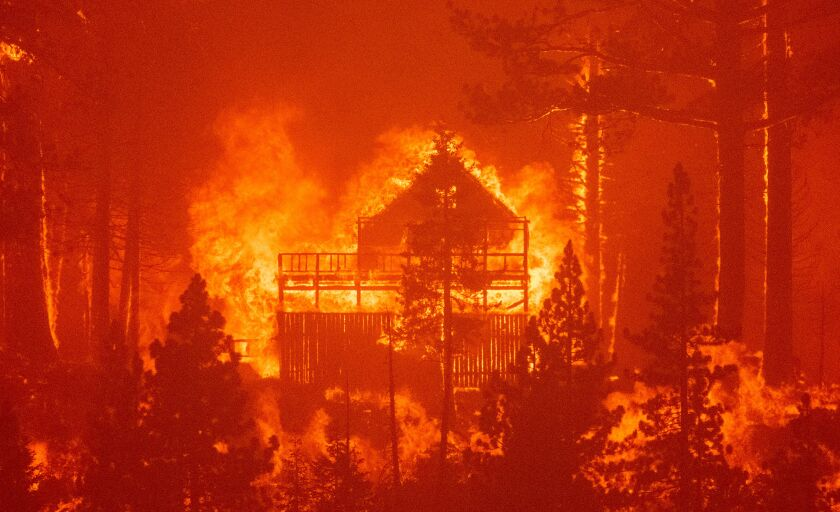 Flames consume multiple homes amid trees and an orange glow