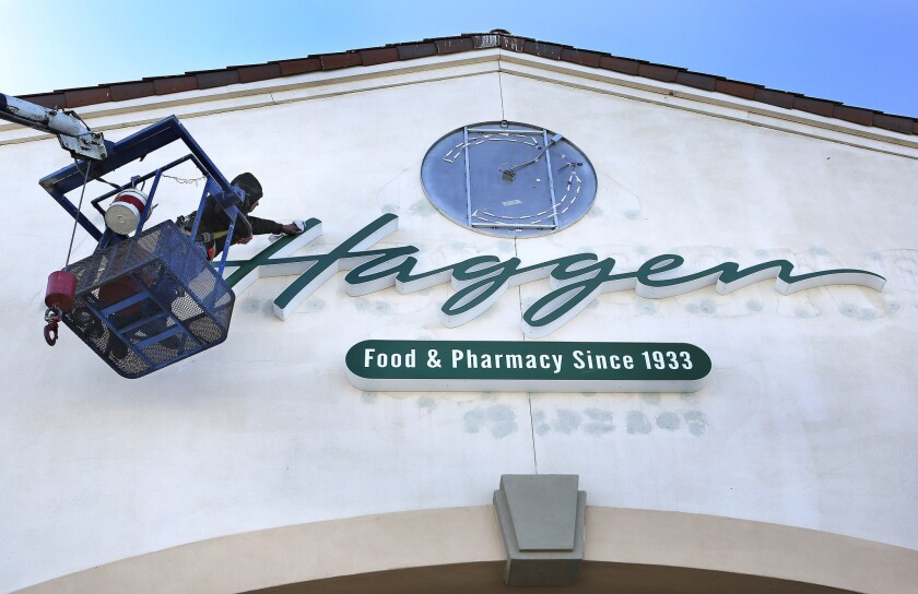 A construction worker wipes away dust after installing a new sign in front of a Haggen grocery store, formerly an Albertsons, in Palmdale, in March. The chain, which has struggled since rapidly expanding this year, is closing 16 supermarkets in California.