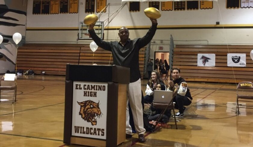 Former Raiders receiver Dokie Williams holds two of the Golden Footballs awarded to El Camino High.