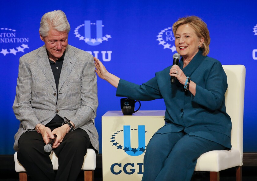 Former President Bill Clinton, left, listens as former Secretary of State Hillary Rodham Clinton speaks during a student conference for the Clinton Global Initiative University at Arizona State University in Tempe, Ariz.