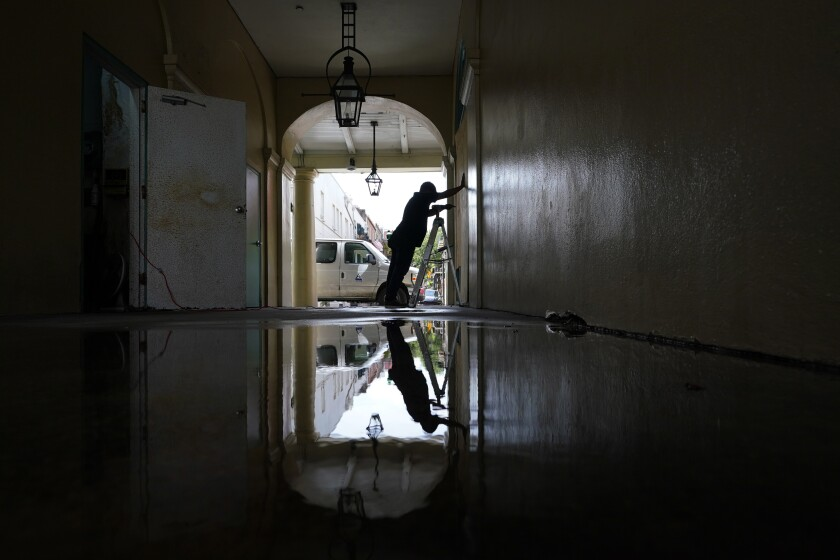 Un trabajador coloca tableros de madero en ventanas y puertas de un negocio en el Barrio Francés de Nueva Orleans